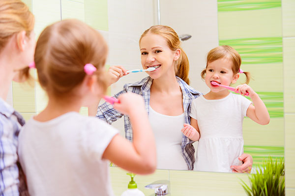 Mother and Daughter brushing their teeth like their Salem dentist at Fairmount Dental Center showed them too.